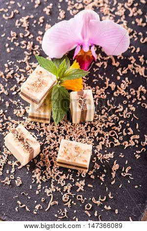 Several Nougat Cubes On Slate Plate With Orchid Bloom