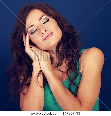 Beautiful Makeup Tired Woman Want To Sleep And She Lying On Her Hands On Blue Background. Closeup To