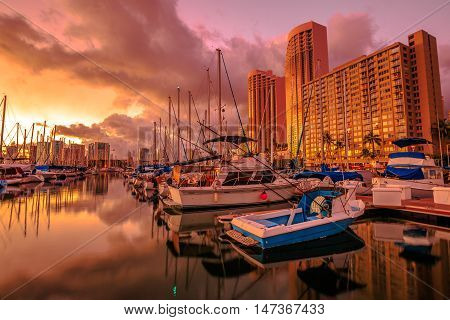 Landscape of sailing boats and yachts docked at the Ala Wai Harbor the largest yacht harbor of Hawaii reflecting in the sea at sunset.On background a luxurious hotel near Waikiki beach in Honolulu.