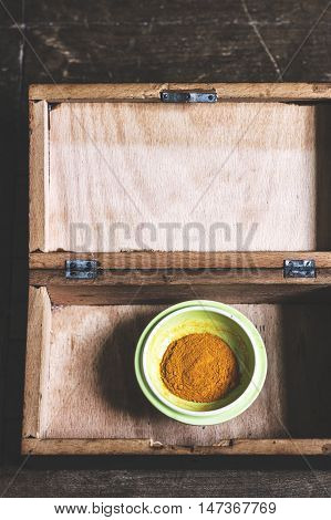 Turmeric powder on a green plate in a wooden box.