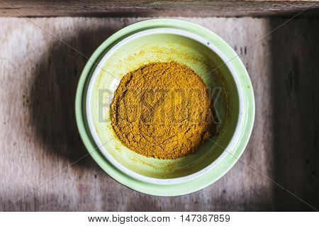 Turmeric powder on a green plate in a wooden box. Closeup