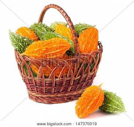 bitter melon or momordica in a wicker basket isolated on white background.