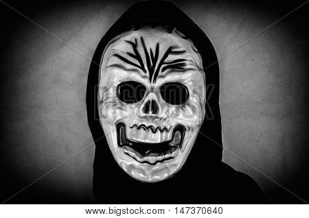 Woman in black with a human skull mask. Low key. Computer added dirt, scratches, grain and vignette.