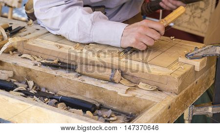 Making craftsman carving wood in a medieval fair, carpentry tools