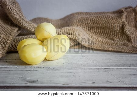 Group of peeled potatoes on white wooden table.