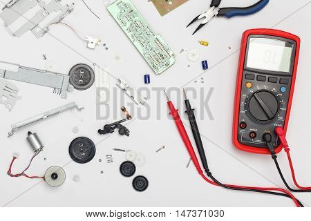 Engineering mess background with multimeter electrical and mechanical parts. View above