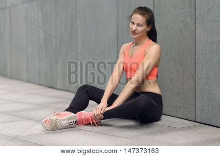 Athletic Young Woman Sitting On The Ground