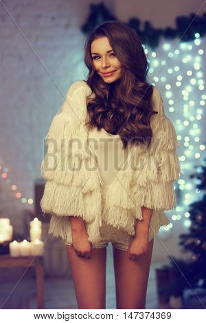 Cute yong woman wearing stylish clothes posing in loft christmas decorated inteior.