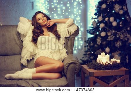 Fashion style portrait of young beautiful trendy girl sitting on sofa in christmas decorated interior. Table with candles, cristmas tree and garland lights bokeh