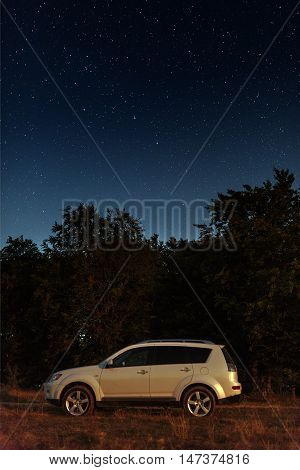 4x4 car at night under the stars near the forest