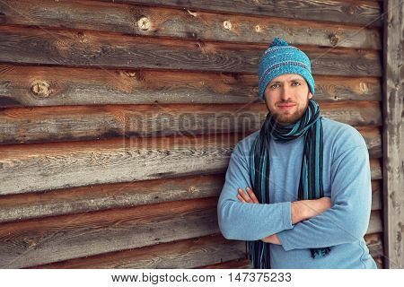handsome unshaven man in winter clothes standing near his house