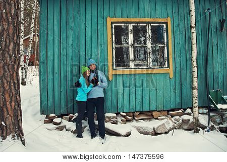 Young happy couple in love outdoors in the winter. Man and woman in winter clothes on a wooden background