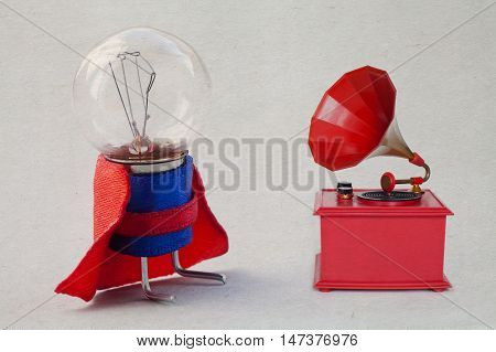 Light bulb in super hero costume. Vintage red color gramophone. Retro plastic toy. Old paper background