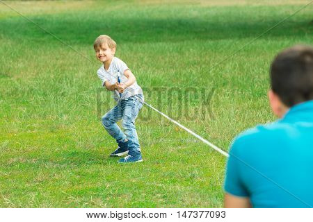 Happy Kid Pulling A Rope In Tug Of War At The Park With His Father