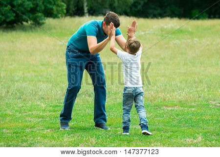 Little Boy Giving High Five To His Father In Park