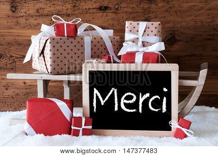 Chalkboard With French Text Merci Means Thank You. Sled With Christmas And Winter Decoration. Gifts And Presents On Snow With Wooden Background.