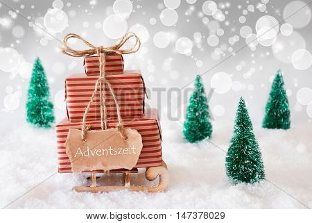 Sleigh Or Sled With Christmas Gifts Or Presents. Snowy Scenery With Snow And Trees. White Sparkling Background With Bokeh Effect. Label With German Text Adventszeit Means Advent Season