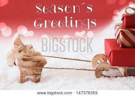 Moose Is Drawing A Sled With Red Gifts Or Presents In Snow. Christmas Card For Seasons Greetings. Red Christmassy Background With Bokeh Effect. English Text Seasons Greetings