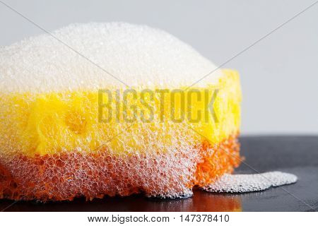 Cleaning sponge with soap foam on top. Macro view bubble suds, gray background.