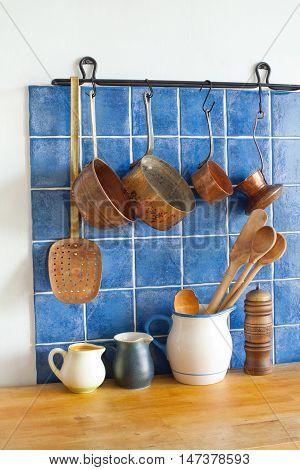 Kitchen accessories. pots jug pan wooden spoons, cooper ladle stewpan.