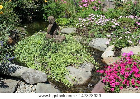 A rock and flower garden with a statue in the center surrounded by water.