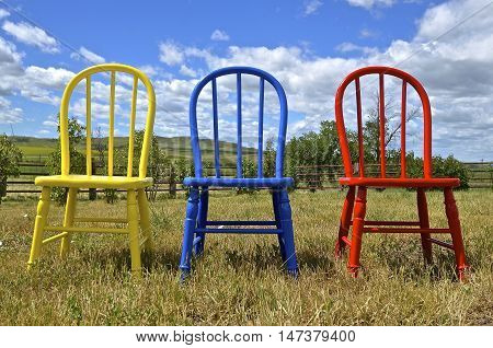 Three colorful painted Windsor wood chairs are lined up in an outdoor setting.