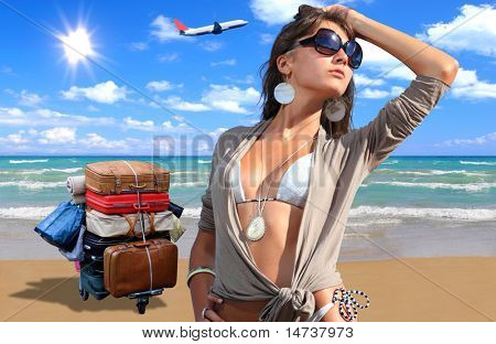 Young woman in bikini on the beach with suitcases and airplane on background