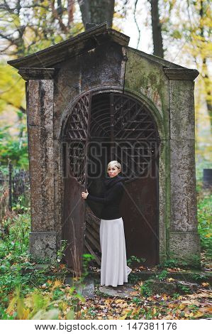 Young stylish blonde in a black jumper and long white skirt stands near a monument in the cemetery holding his hands behind iron gates and looks at the camera.
