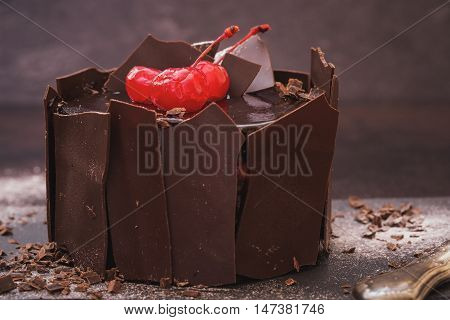 Chocolate cake surrounded with chocolate pieces and red cherries on top. Selective focus, vintage and dark toned