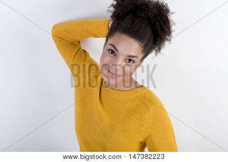 Smiling young brunette woman wearing warm yellow clothes over bright background