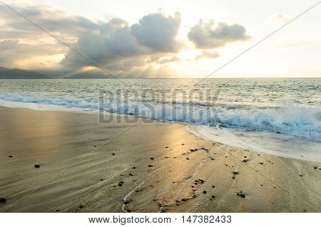 Ocean sun rays is a bright uplifting seascape with sun beams breaking through the clouds as a gentle wave rolls to shore.