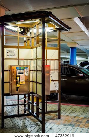 Honolulu, Hawaii, USA - Dec 21, 2015: Night view of public telephone booth at the popular Ala Moana Center. The booth has a opened modern Japanese design.