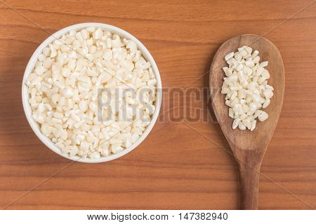White grated corn kernels into a bowl over a wooden table