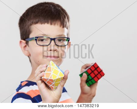 Portrait of smart cute kid little boy in glasses with magic rubik cube and platonic solid geometric figure. Education.
