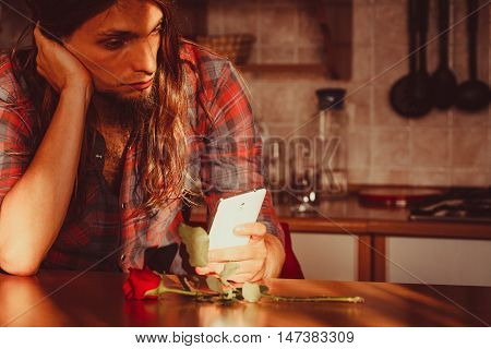 Worried Man With Rose And Mobile Phone.
