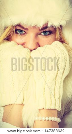 Winter clothing people fashion concept. Blonde woman with fur cap. Attractive lady has white outfit and gloves.