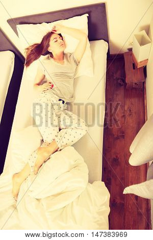 Mornings people concept. Sleepy woman sleeping in the bed. Attractive lady changing sleep positions.