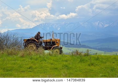 PIENINY MOUNTAINS POLAND - MAY 11 2016: The old man working on a tractor in the countryside in Pieniny Mountains Poland.