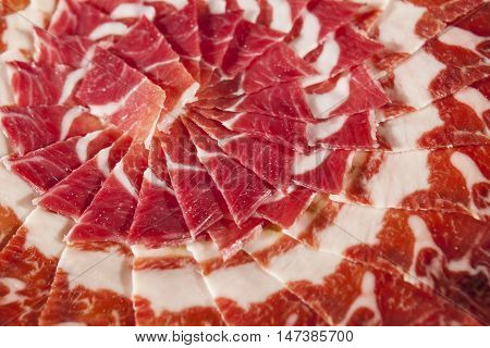 Circular decorative arrangement of iberian cured ham on plate. Selective focus point