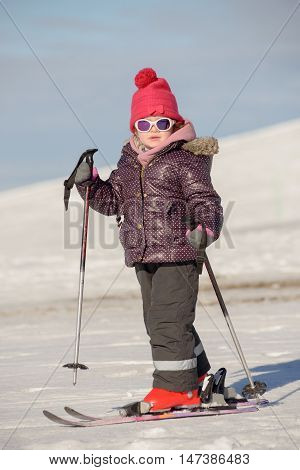 a happy little girl with hat  skiing downhill