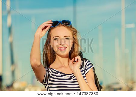 Summer relaxation concept.. Portrait girl with blue heart shaped sunglasses enjoying summer breeze outdoor in marina