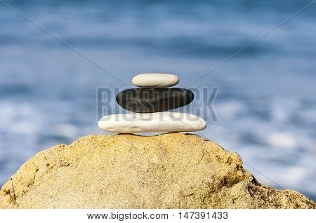 Stones balance vintage retro instagram like hierarchy stack over blue sea background. Spa or well-being freedom and stability concept on rocks.
