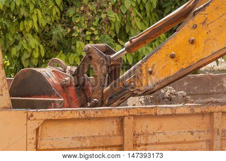 Excavator working machine loading soil or sand into truck body.