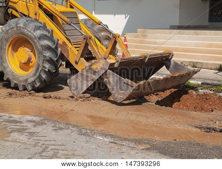 Excavator working on the Repair of pipe water and sewerage on a road Worker  to dig a hole
