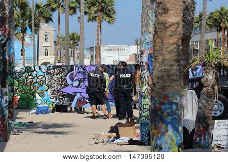 Venice Beach, Los Angeles, California, 9/10/16--Homeless woman under arrest by Los Angeles Police Department officers. Her possessions are confiscated as wall is spray painted in background. Police confront homelessness and urban blight in cities.