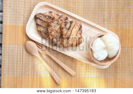 Thai food - grilled pork and sticky rice on wood plate