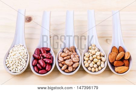 Assortment Of Beans And Lentils In Spoon On Wooden Background. Almond, Soybean, Red Kidney Bean ,red