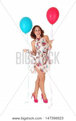 A gorgeous young woman standing in a dress with balloons attached lifting her dress isolated for white background.