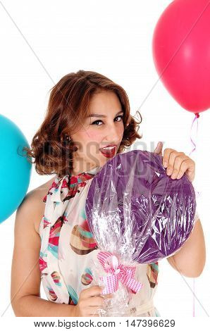 A closeup image of a gorgeous young woman with a big lolly-pop and balloons isolated for white background.
