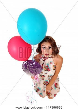 A beautiful woman kneeling on floor and looking up with a lollypop and two balloons isolated for white background.